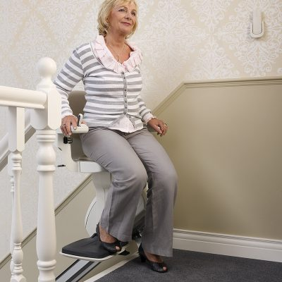 Lady getting off one of the Homeglide stair lifts for sale