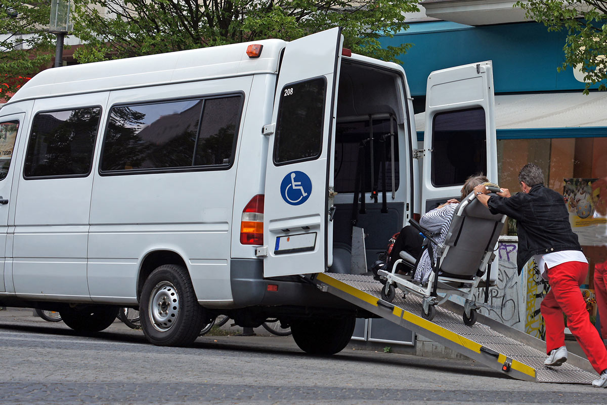 Wheelchair user being pushed up ramp of handicap van